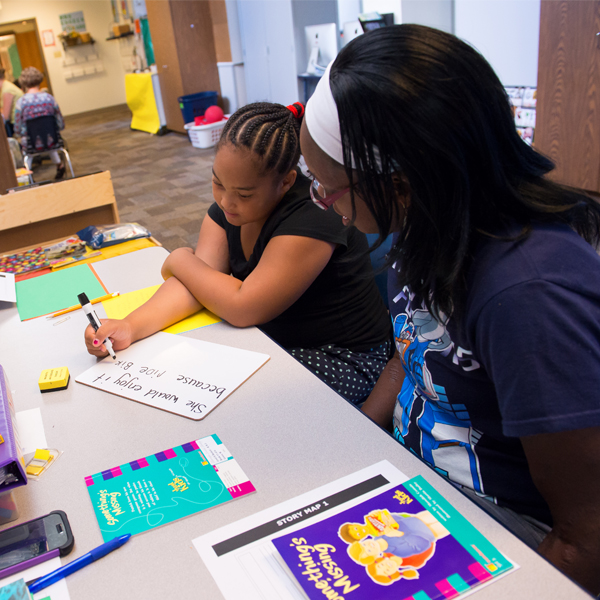 Elementary teacher working with student at table